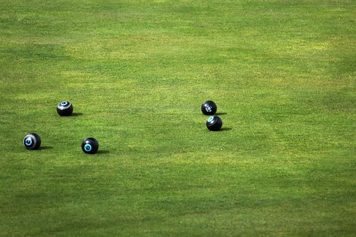 Five bowls lying on Ilford Bowling Green
